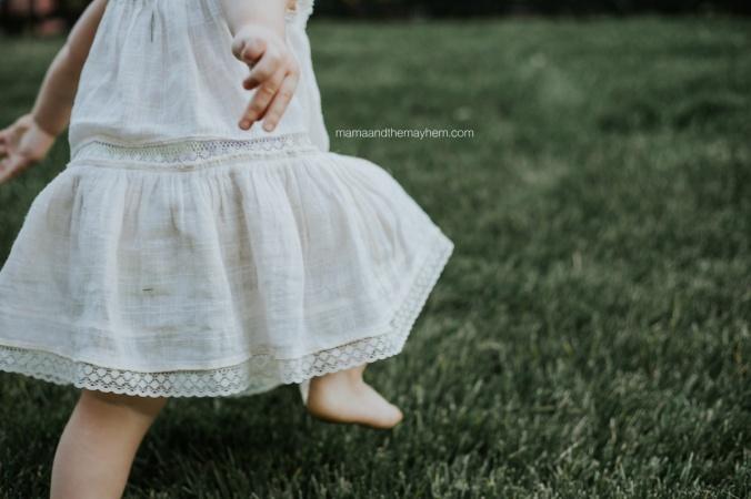 little-girl-in-white-dress-running-in-grass
